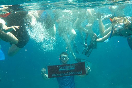 Students under water holding sign for Northeast